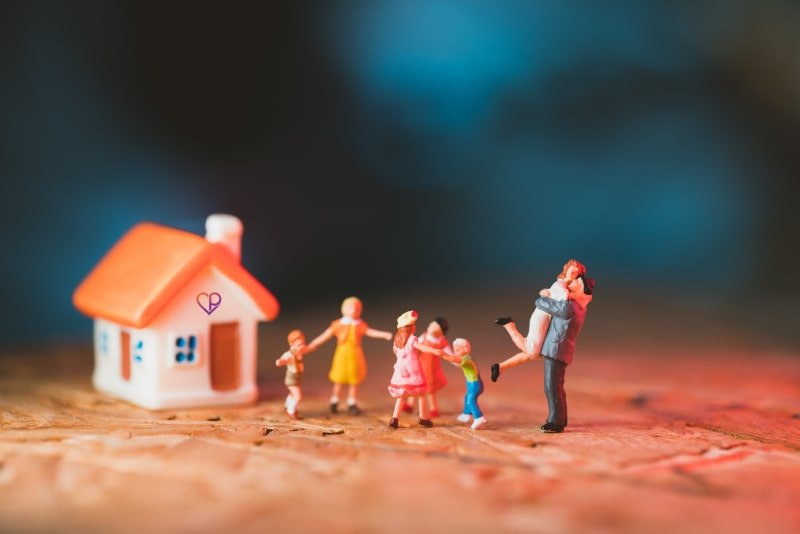 small figurines showing family celebrating as they have a new house with a new mortgage covered with life insurance and critical illness cover