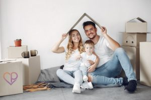 young family moving into new house they have purchased. They are holding a cardboard box over their head to illustrate life insurance and critical illness cover. the young handsome couple have a young child