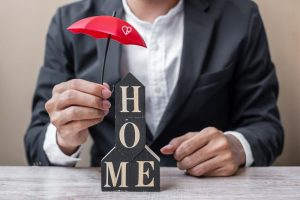 "man holding a red umbrella over blocks that spell out ""home"". This represents mortgage life insurance and critical illness cover. The man is well dressed in a nice suit."