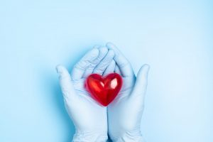 blue gloves holding a heart